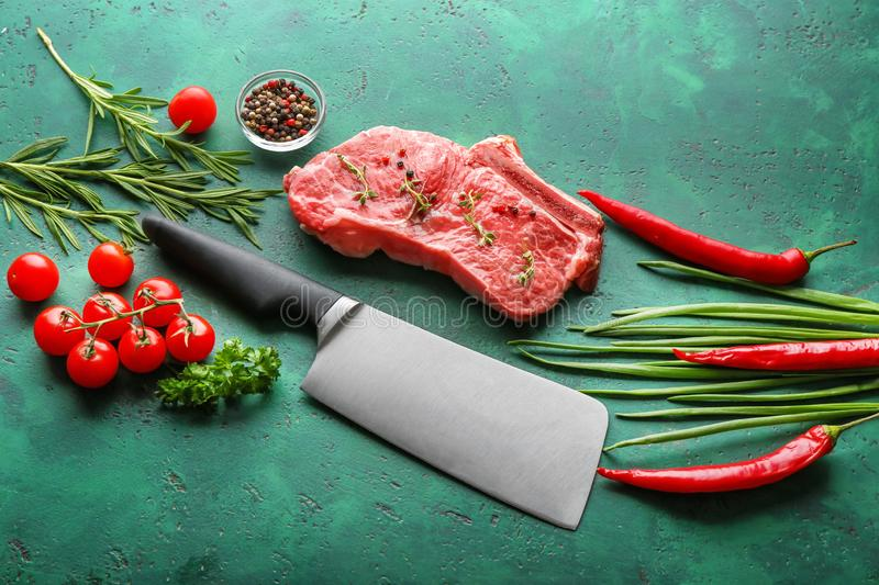Fresh raw meat with vegetables, herbs and spices on color background royalty free stock images