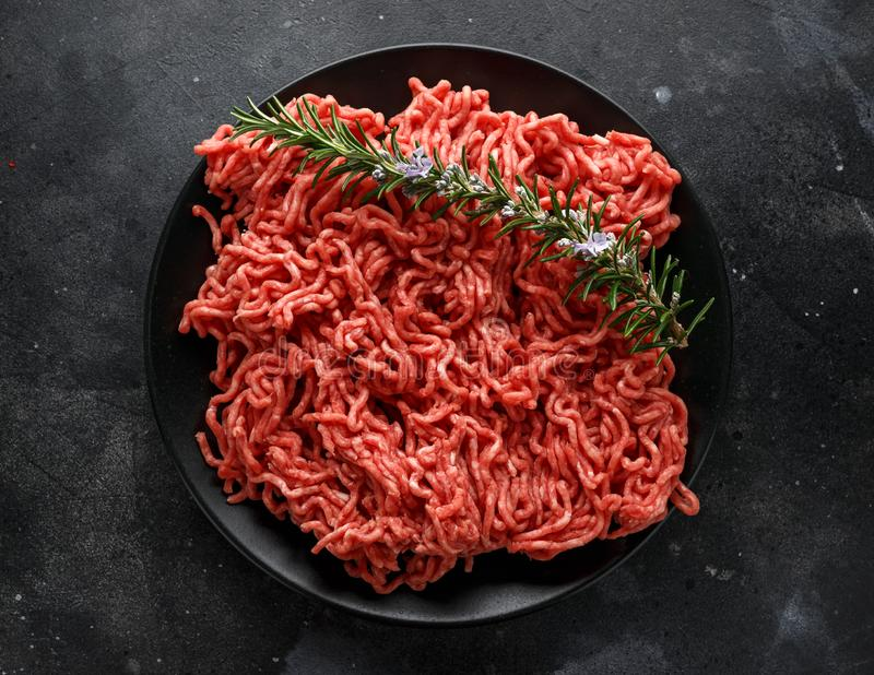 Fresh Raw mince, Minced beef, ground meat with herbs and spices on black plate.  royalty free stock image