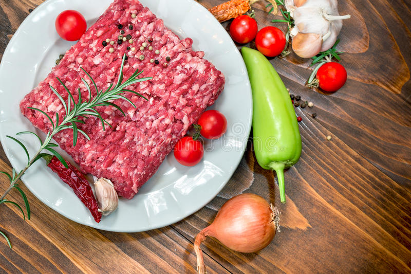 Fresh raw minced beef - ground beef on white plate and vegetables. Raw fresh ground beef meat - minced meat on plate and spice (seasoning) with vegetable stock photo