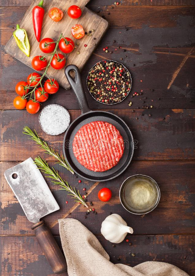 Fresh raw minced homemade farmers grill beef burger in frying pan with spices and herbs and meat hatchet on wooden board. Oil, royalty free stock photos