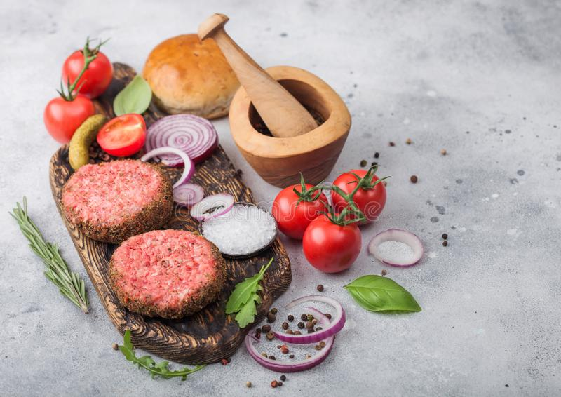 Fresh raw minced pepper beef burgers on vintage chopping board with buns onion and tomatoes on wooden background.Mortar with stock photo