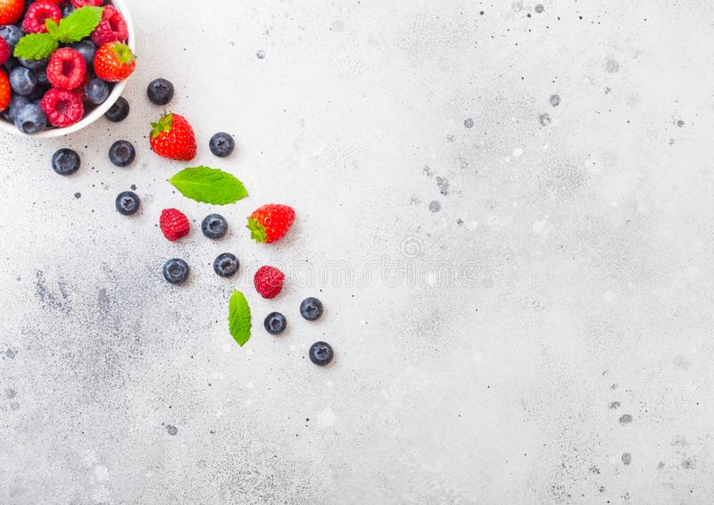 Fresh raw organic berries isolated in white ceramic bowl plate on kitchen table background. Top view. Strawberry, Raspberry, Blueb royalty free stock photo