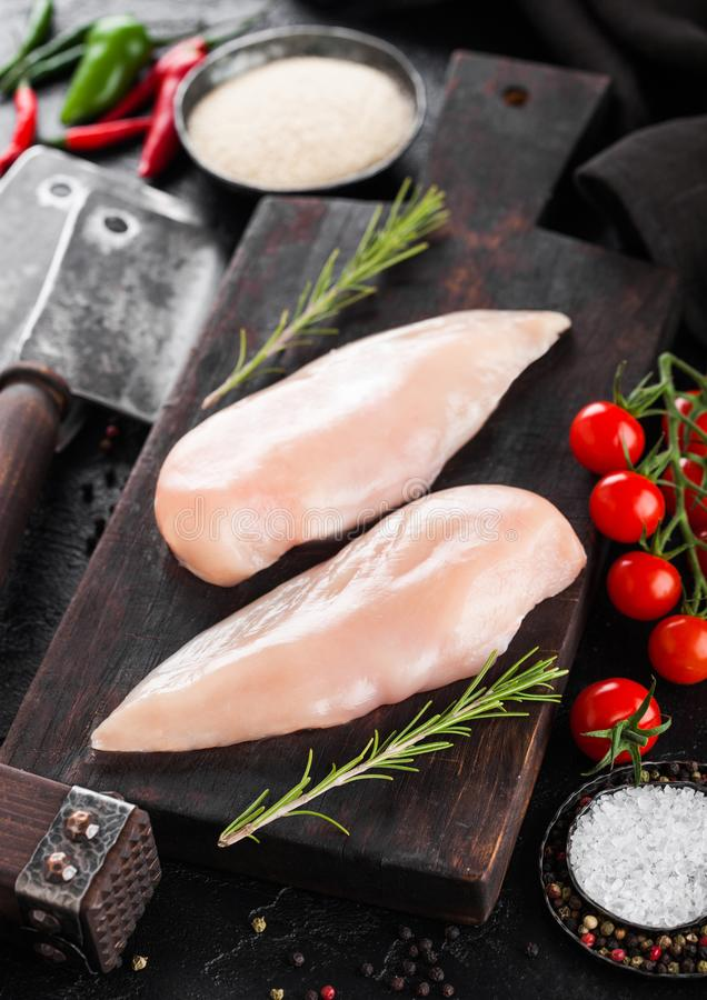 Fresh Raw Organic Chicken Fillet Breast on vintage board with meat hatchets and spices with herbs on wooden background. Tomatoes royalty free stock image