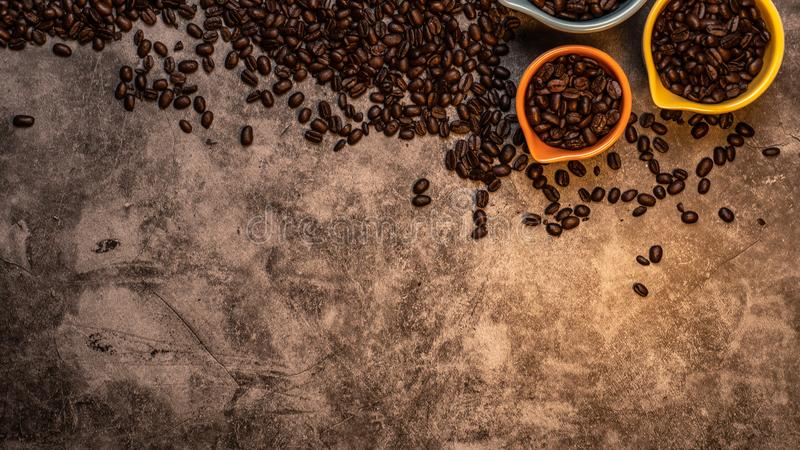 Fresh raw organic coffee beans in colorful cups with varied sizes scattered on a slate countertop background. Fresh raw organic coffee beans in colorful cups royalty free stock photography