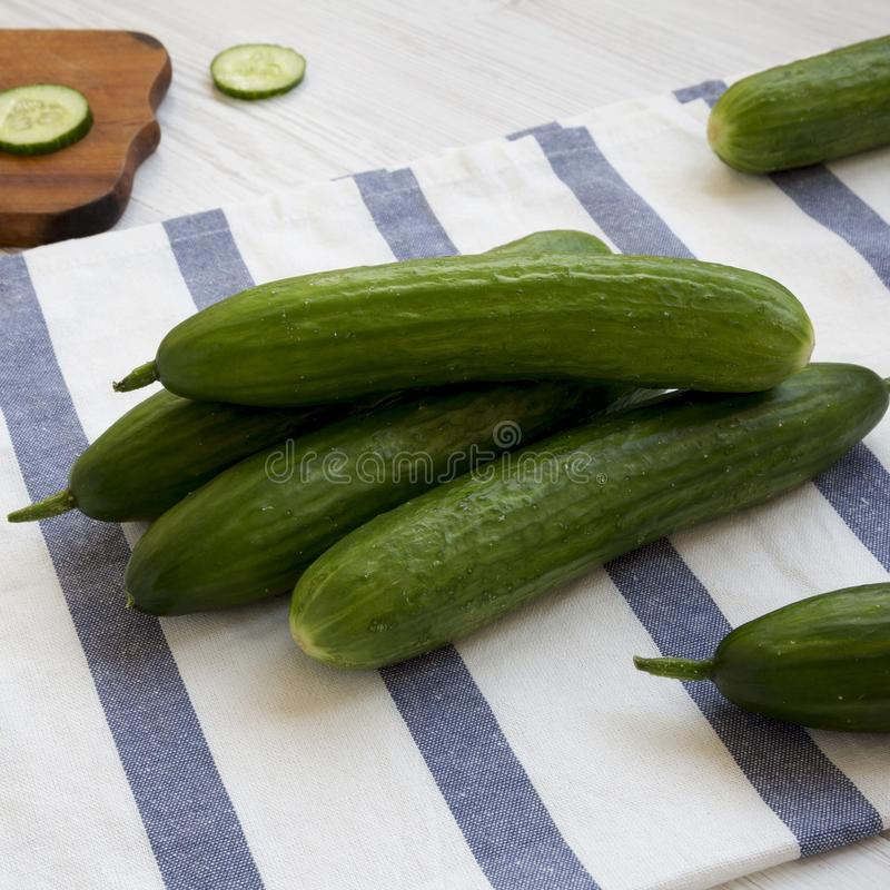 Fresh raw organic green cucumbers on cloth, side view. Closeup stock image