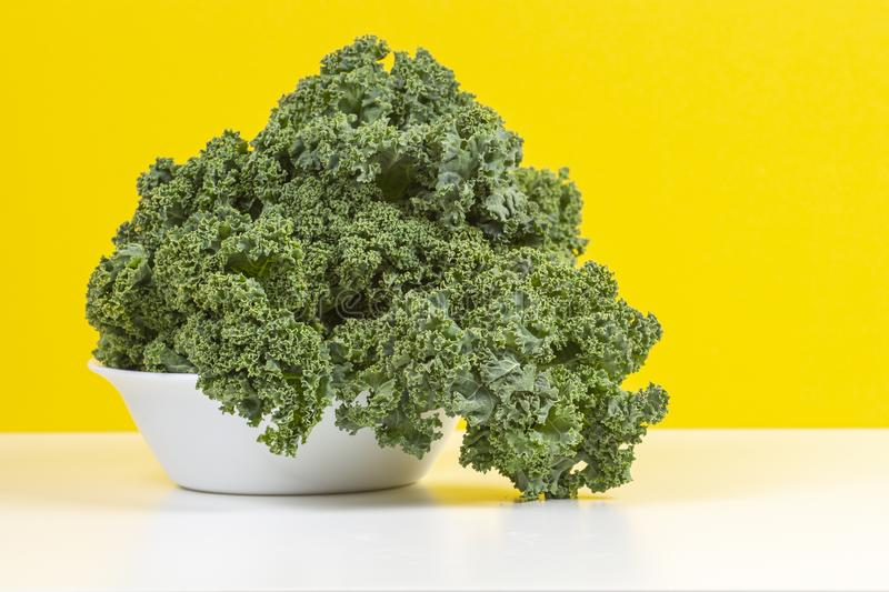 Fresh raw organic green curly kale leaves of kale on white plate with yellow background.  royalty free stock photos