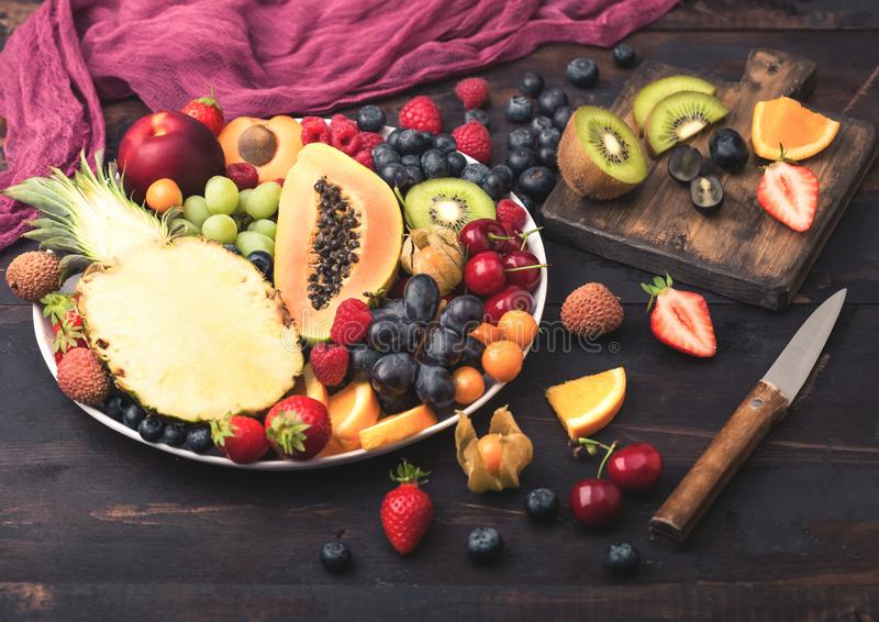 Fresh raw organic summer berries and exotic fruits in white plate on dark wooden background with chopping board and knife. Pineapple, papaya, grapes, nectarine royalty free stock photos