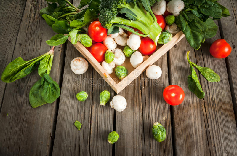 Fresh raw organic vegetables on a rustic wooden table in basket: spinach, broccoli, Brussels royalty free stock images