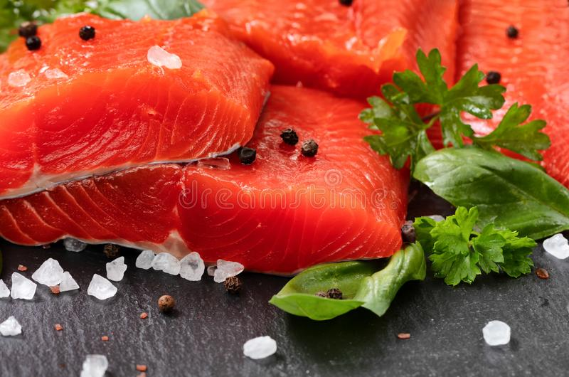 Fresh raw pacific wild sockeye salmon fillets on natural stone with spices and basil leaves. Fresh raw copper river sockeye salmon fillets on natural stone with royalty free stock image