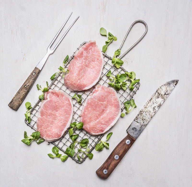 Fresh raw pork steaks with herbs, a knife and fork for the meat on the grill for roasting wooden rustic background top view. Fresh raw pork steaks with herbs, a royalty free stock images