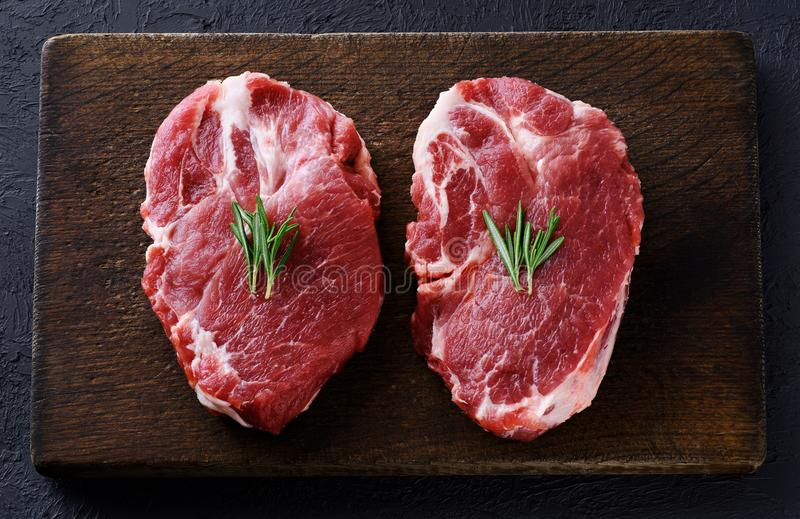 Fresh raw pork steaks and rosemary on a dark wooden background. royalty free stock photo