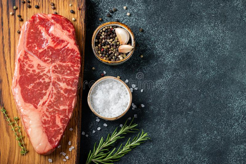 Fresh raw Prime Black Angus beef steaks with spices on wooden board: Striploin, Rib Eye. Top view with copy space. On a dark backg stock photos