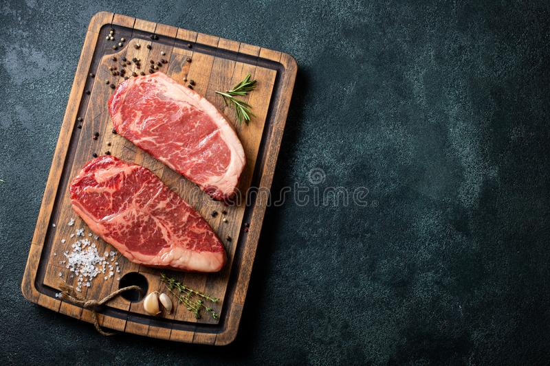 Fresh raw Prime Black Angus beef steaks with spices on wooden board: Striploin, Rib Eye. Top view with copy space. On a dark backg. Round royalty free stock photo