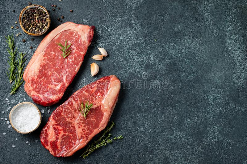 Fresh raw Prime Black Angus beef steaks on stone board: Striploin, Rib Eye. Top view with copy space. On a dark background royalty free stock image