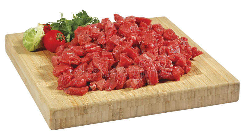 Fresh raw red cubed meat chunk on wooden cut board isolated over white background royalty free stock images