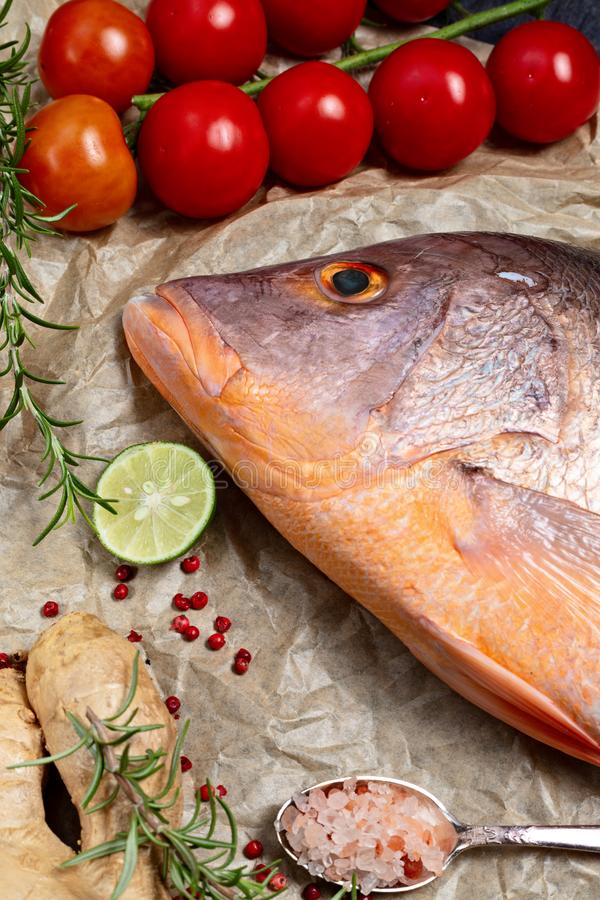 Fresh raw red snapper fish with spices , herbs and vegetables for cooking on brown backing paper . Top view, vertical composition.  stock images