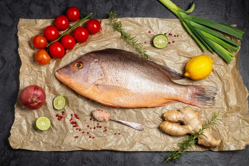 Fresh raw red snapper fish with spices , herbs and vegetables for cooking on brown backing paper . Top view. stock photos