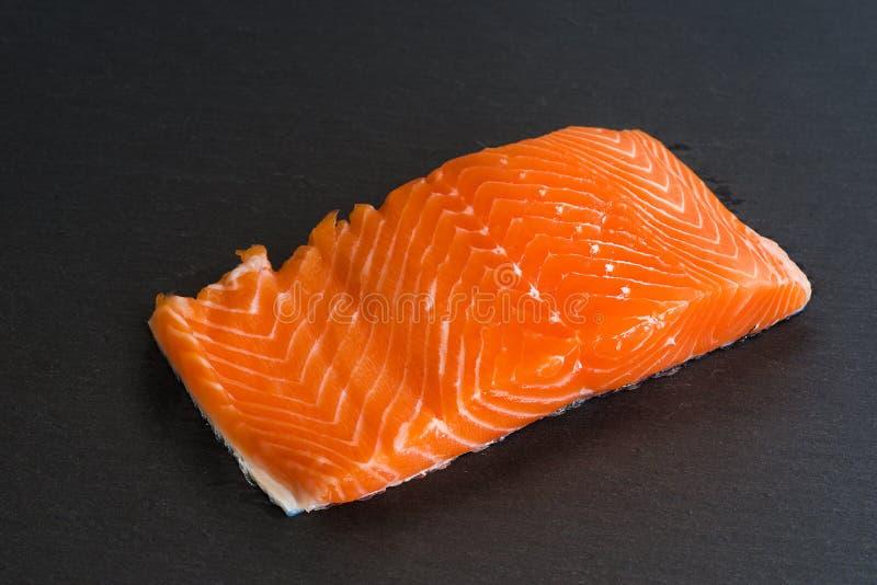 Fresh raw salmon filet on black background royalty free stock photo