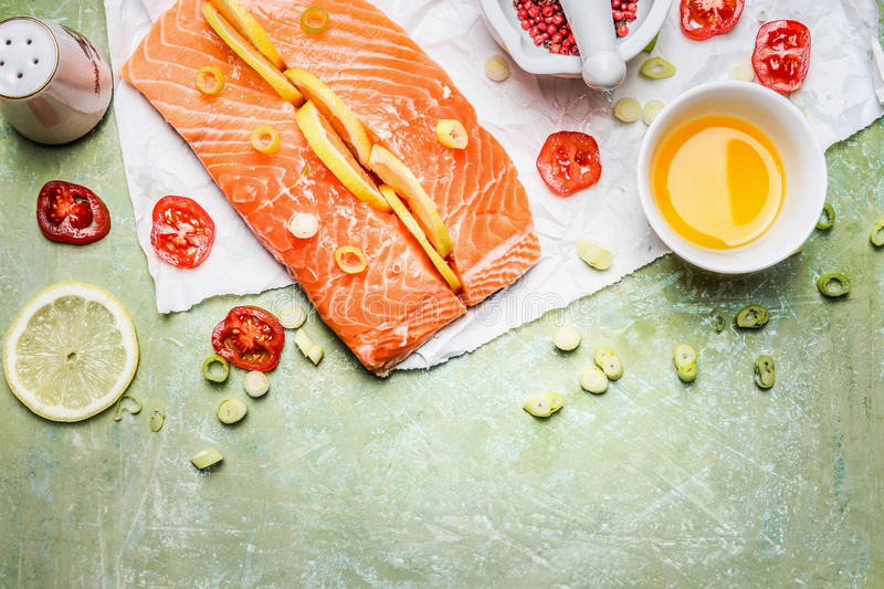 Fresh raw salmon fillet with oil and cooking ingredients on rustic background, top view, border. stock photo