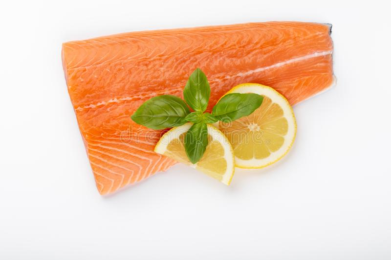 Fresh raw salmon fillets with herbs and lemon isolated on white background royalty free stock photo
