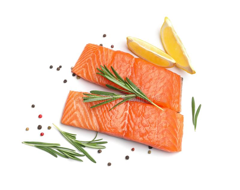 Fresh raw salmon fillets with  and lemon on white background, top view. Fresh raw salmon fillets with rosemary and lemon on white background, top view royalty free stock photography