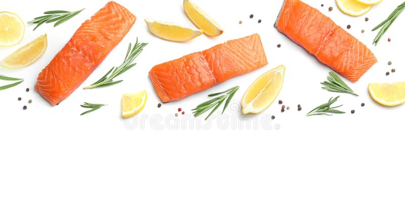 Fresh raw salmon fillets with rosemary and  on white background, top view. Fresh raw salmon fillets with rosemary and lemon on white background, top view royalty free stock photography