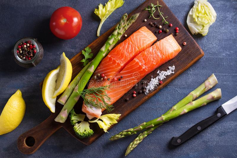 Fresh raw salmon fish fillet, asparagus, lemon, herbs and spices royalty free stock images