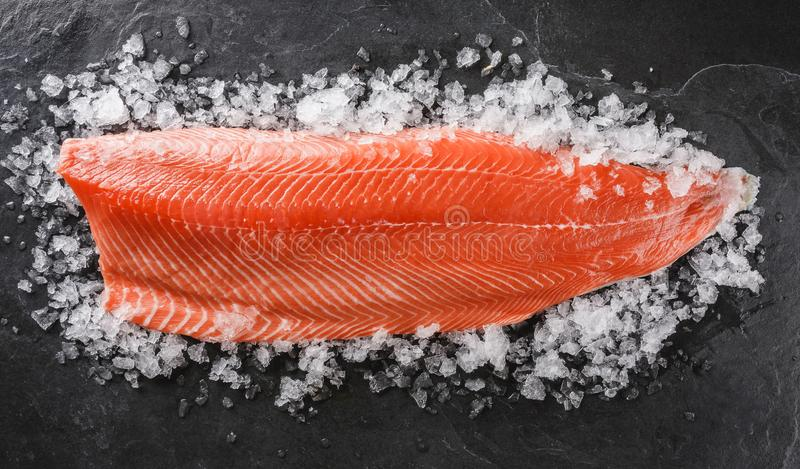 Fresh raw salmon fish steak with spices on ice over dark stone background. stock photo