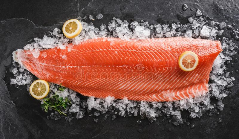 Fresh raw salmon fish steak with spices on ice over dark stone background. Creative layout made of fish, top view, flat lay.  stock photos