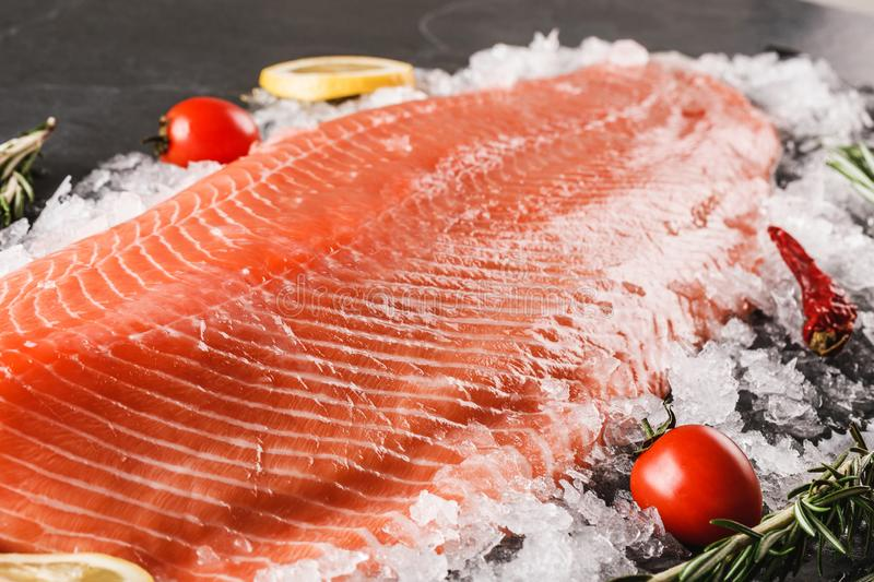 Fresh raw salmon fish steak with spices on ice over dark stone background. Creative layout made of fish, macro stock image