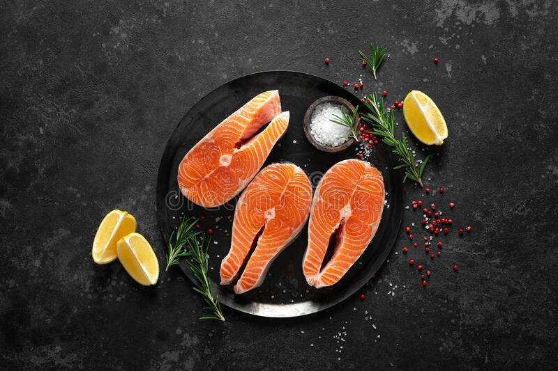 Fresh raw salmon fish steaks with cooking ingredients on kitchen table, healthy food, source of omega-3 royalty free stock photos