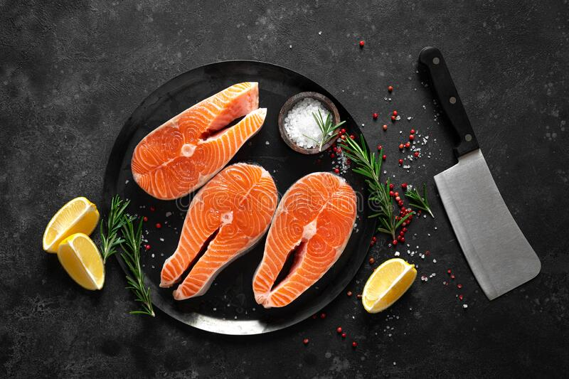 Fresh raw salmon fish steaks with cooking ingredients on kitchen table, healthy food, source of omega-3 stock photo