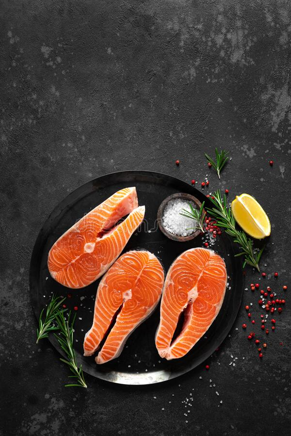 Fresh raw salmon fish steaks with cooking ingredients on kitchen table, healthy food, source of omega-3. Top view stock images