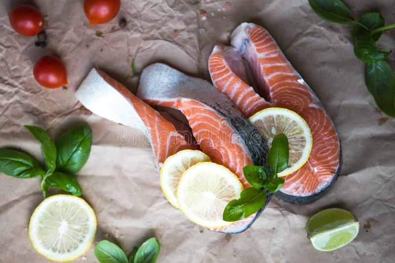 Fresh raw salmon fish steaks on wooden background with ingredients for cooking. Closeup. Top view stock photos
