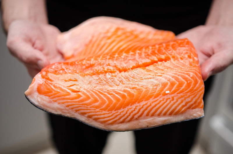 Fresh raw salmon. Hands holding large file of raw salmon royalty free stock photos