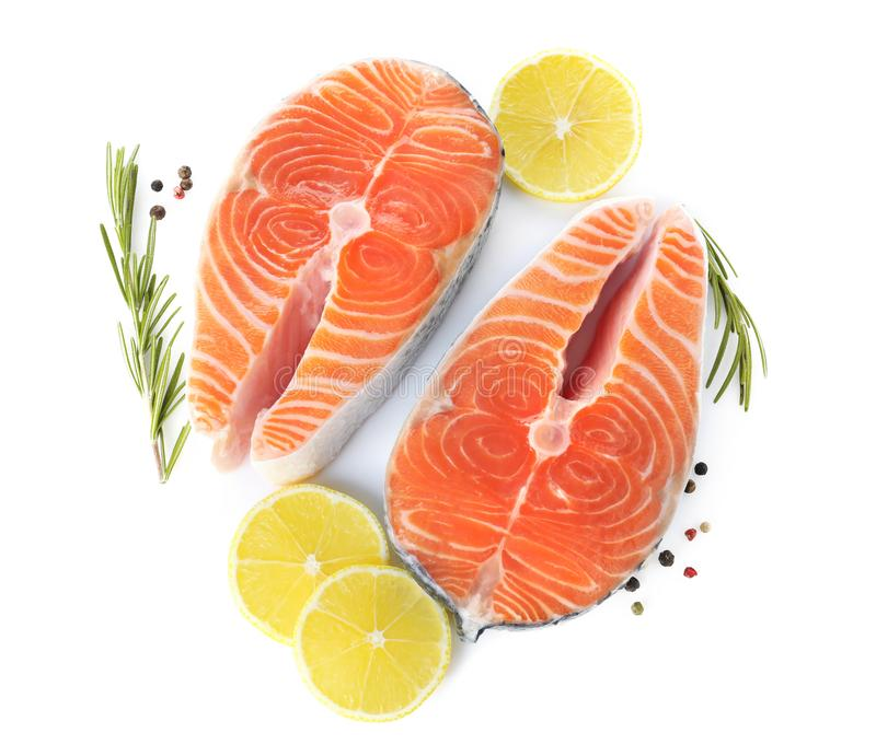 Fresh raw salmon with lemon, pepper and rosemary on background, top view. Fish delicacy. Fresh raw salmon with lemon, pepper and rosemary on white background stock image