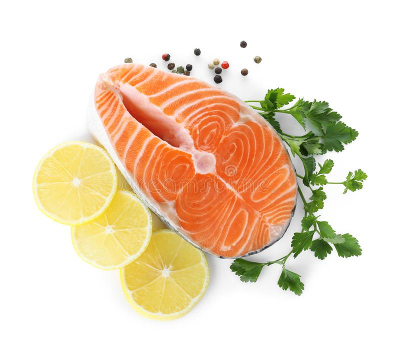 Fresh raw salmon with pepper, lemon and parsley on background, top view. Fish delicacy. Fresh raw salmon with pepper, lemon and parsley on white background, top stock image