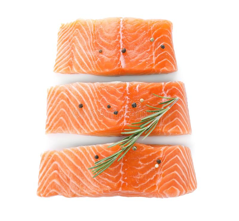 Fresh raw salmon with pepper and rosemary on background, top view. Fish delicacy. Fresh raw salmon with pepper and rosemary on white background, top view. Fish stock images