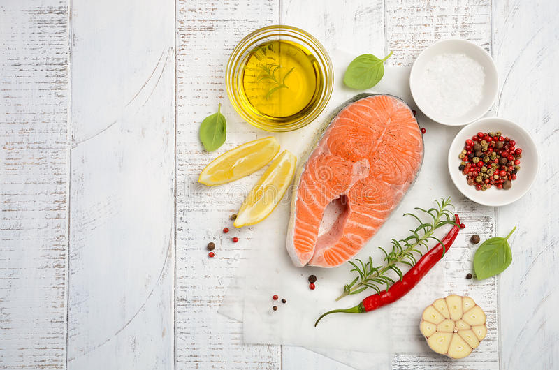 Fresh raw salmon steak with lemon, olive oil and spices on rustic wooden background. Ingredients for making healthy dinner. Health. Y diet concept. Top view stock photo