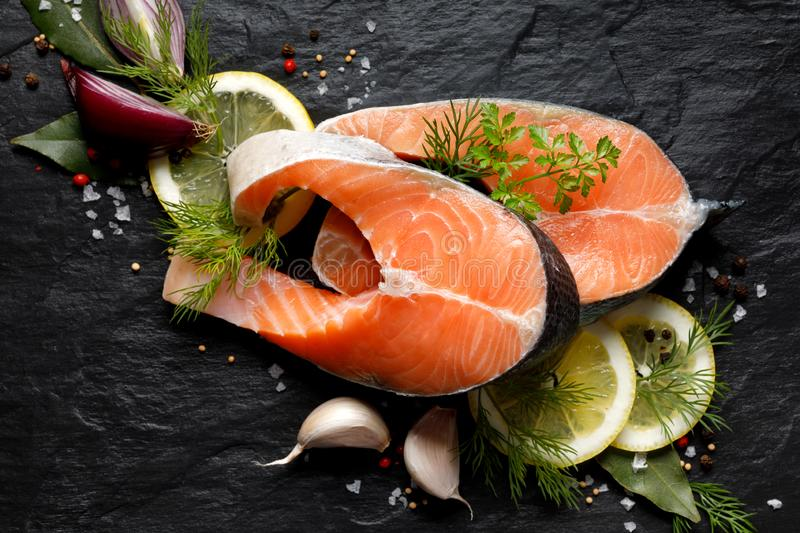 Fresh, raw salmon steaks with the addition of slices of lemon, garlic, onion, herbs and spices on a black stone background, top vi stock photo