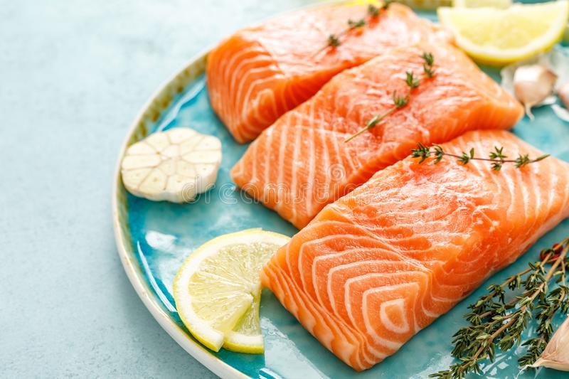 Fresh raw salmon or trout fillets with ingredients stock photos