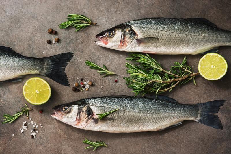 Fresh raw sea bass fish with rosemary and lime on a dark brown rustic background. Flat lay, overhead view stock images