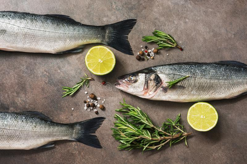 Fresh raw sea bass fish with rosemary and lime on a dark brown rustic background. Flat lay, overhead view stock photo