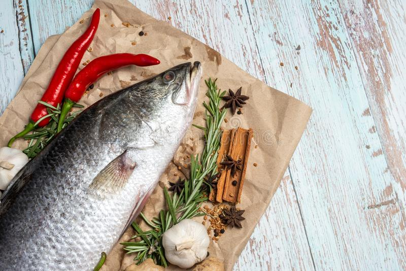 Fresh Raw Sea Bass on wooden table. Fresh Raw Sea Bass on wooden table surrounded by fresh ingredients and spices royalty free stock photos