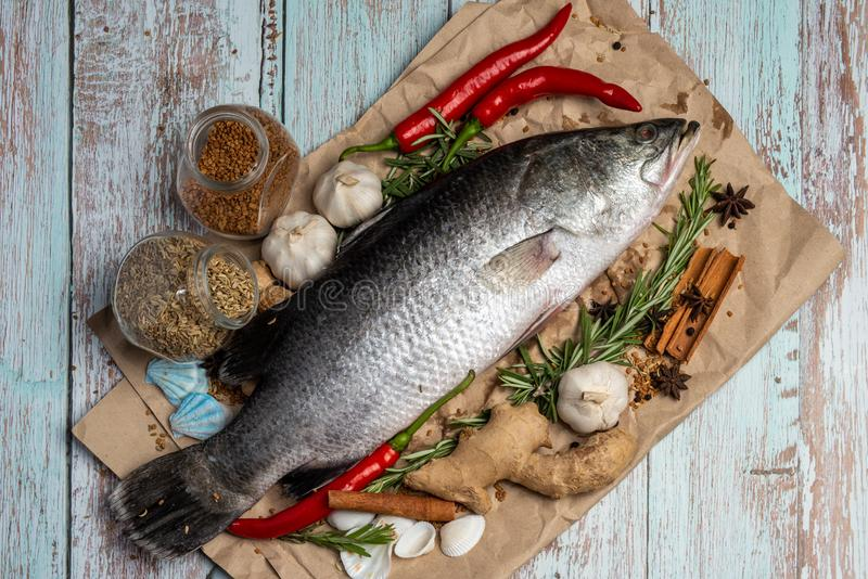 Fresh Raw Sea Bass on wooden table surrounded by fresh ingredients and spices. Fresh Sea Bass on wooden table surrounded by spices royalty free stock image