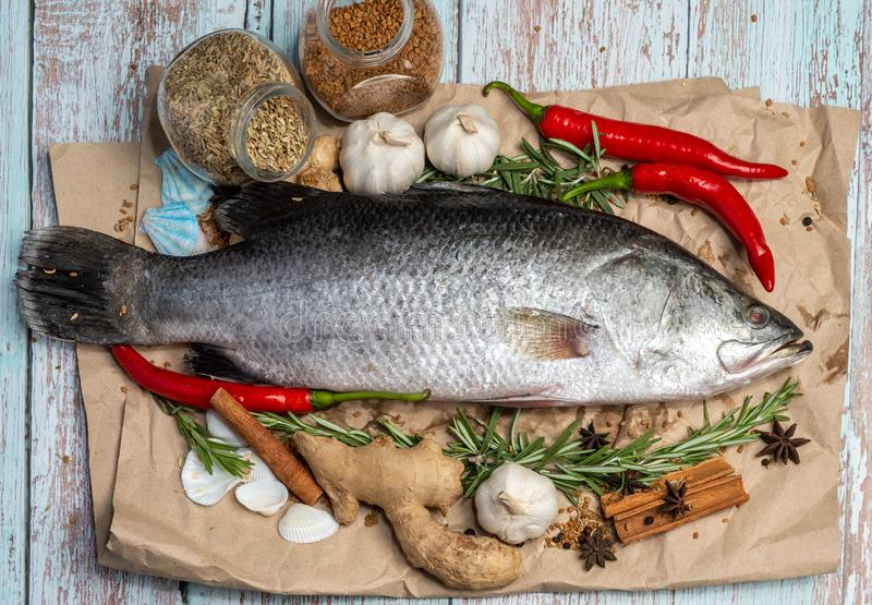 Fresh Raw Sea Bass on wooden table surrounded by fresh ingredients and spices. Fresh Sea Bass on wooden table surrounded by spices royalty free stock photo