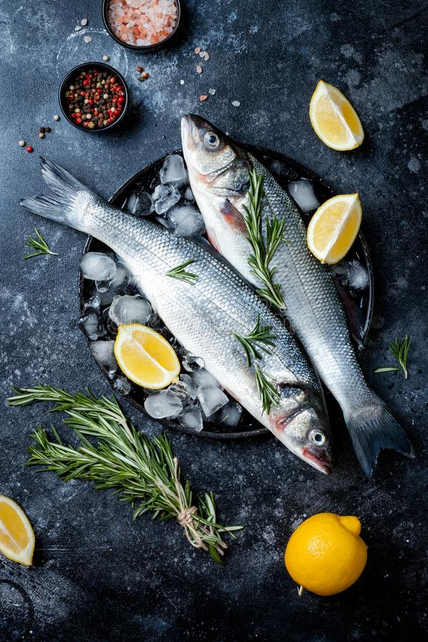 Fresh raw seabass fish on black stone background with spices, herbs, lemon and salt. Culinary seafood background with ingredients. For cooking. Top view royalty free stock photo
