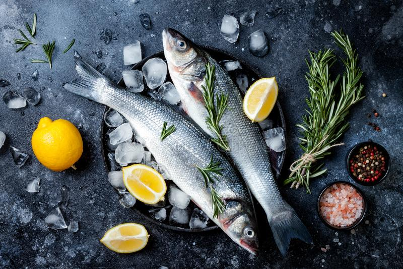 Fresh raw seabass fish on black stone background with spices, herbs, lemon and salt. Culinary seafood background with ingredients royalty free stock photography