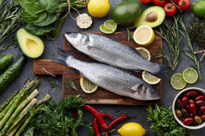 Fresh raw seabass and ingredients for cooking. Rosemary, thyme, lime, lemon, greens and vegetables. Top view stock image