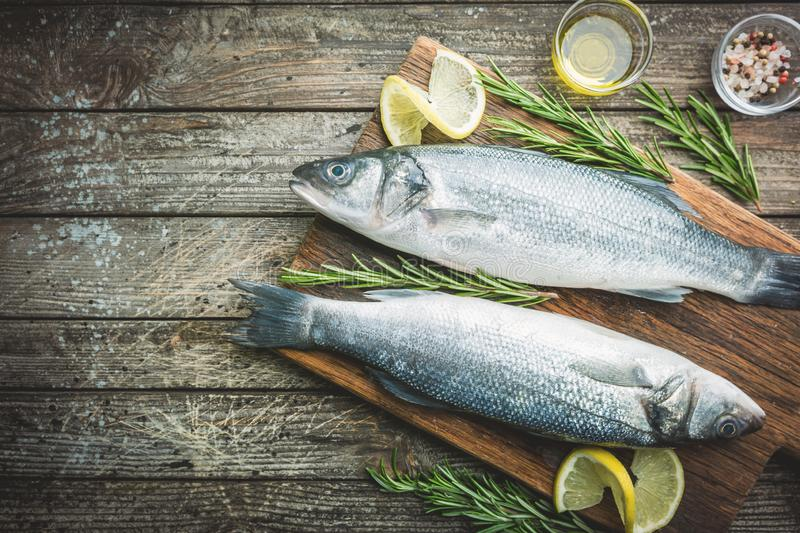 Fresh raw seabass. And ingredients for cooking. Two fish seabass with lemon, spices and herbs on wooden table, top view with copy space royalty free stock photos